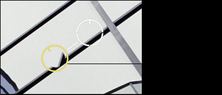 """Abbildung. Gelbe Überlagerung """"Reparaturstempel"""" über einem Bereich mit geklonten Pixeln, deren Winkeln angepasst werden muss."""