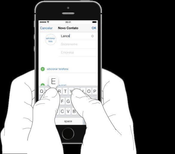 O texto sendo digitado. O iPhone está sendo segurado com as duas mãos, com cada polegar apoiado sobre o teclado. A letra que está sendo digitada aparece acima da tela.